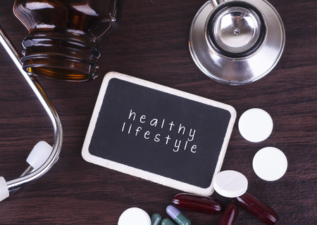 medico: Blackboard, pills and bottle with stethoscope, healthy lifestyle word  on wooden table  with copyspace area