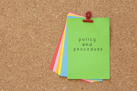 directive: policy and procedures written on color sticker notes over cork board background