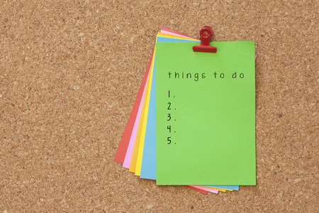 directive: things to do written on color sticker notes over cork board background Stock Photo