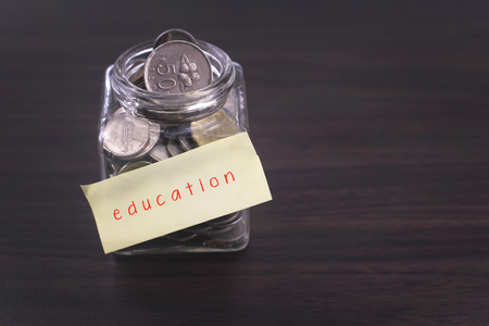 finacial: Finacial concept. Money in the glass on wooden table with education word and copy space area. Stock Photo