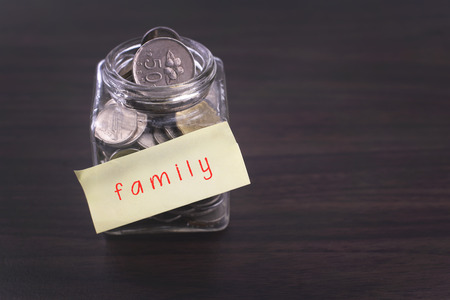 finacial: Finacial concept. Money in the glass on wooden table with family word and copy space area. Stock Photo