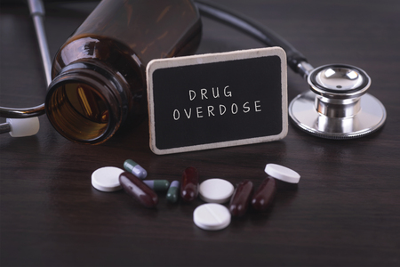 sobredosis: Stethoscope, pill bottle, Various pills, capsules and DRUG OVERDOSE on wooden background with copyspace area.