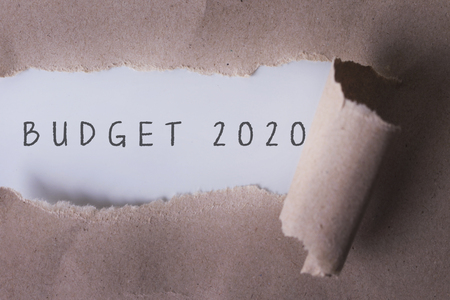 money matters: torn paper with word budget 2020.Copyspace area.