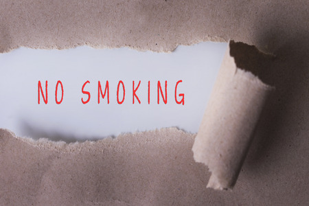 money matters: torn paper with NO SMOKING word. Copyspace area. Stock Photo