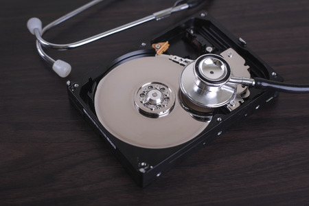 data recovery: Depiction of computer repairs and digital data recovery with a stethoscope scanning for lost information on a hard drive disc.