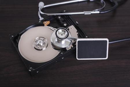 disco duro: Representaci�n de la reparaci�n de computadoras y de recuperaci�n de datos de escaneo digital con un estetoscopio para la informaci�n perdida en un disco en el disco duro. Foto de archivo