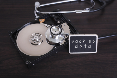 disco duro: A stethoscope scanning for lost information on a hard drive disc with back up data word on board Foto de archivo