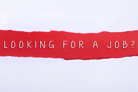 looking for a job: Torn paper with a LOOKING FOR A JOB word on red background.