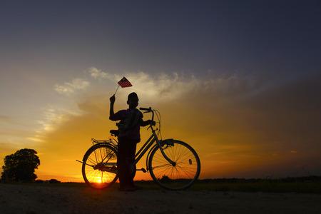 onafhankelijkheid Day concept - Silhouet van jonge lokale jongen op rijstveld met een Maleisische vlag tijdens zonsondergang