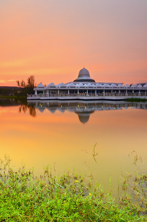 vibrant colours: Beautiful white mosque during burning sunrise with mirror reflection on the lake. Vibrant colours