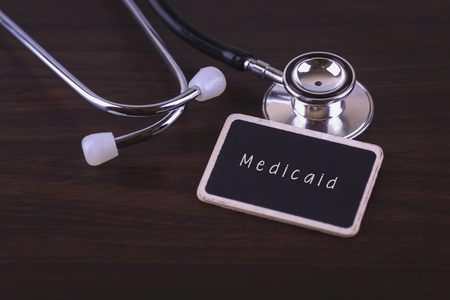medicaid: Stethoscope on wood background with Medicaid words as medical concept