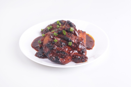 merah: Grilled chicken or ayam golek on white plate, white background. Malaysian traditional cuisine Stock Photo