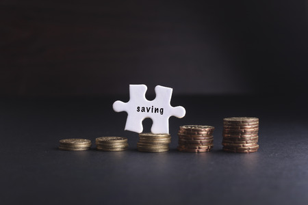 leading education: White missing puzzle and gold coins with saving word ,copyspace area Stock Photo