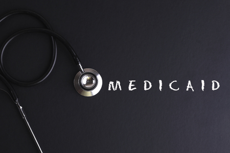 medicaid: MEDICAID word with stethoscope - health concept. Medical conceptual Stock Photo