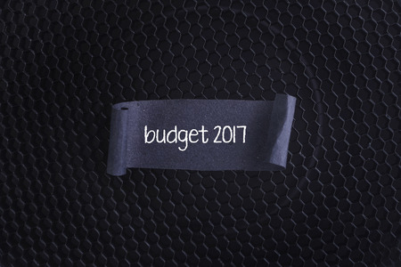 money matters: Black papper with budget 2017 on black texture background.