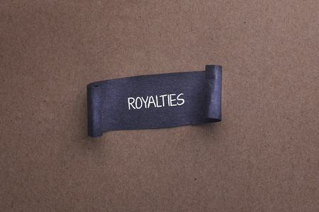 compensated: Black papper with ROYALTIES word on wooden background