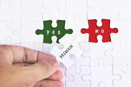 separatism: Business Concept - Female hand and missing puzzle with BREMAIN YES AND NO
