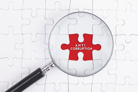corruptible: Business Concept - Magnifier Glass on white puzze with ANTI CORRUPTION Word