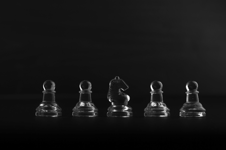 ebony: Solitary black chess piece in genuine ebony wood in focus standing on a glossy table in the dark