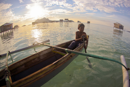 celebes: SIBUAN ISLAND, SABAH, MALAYSIA - MARCH 03 : Unidentified Sea Gypsies boy paddles a boat on March 03, 2014 in Sabah, Malaysia. The Sea Gypsies are sea nomads that move from one place to another. Editorial