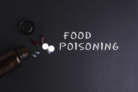 poisoning: FOOD POISONING word with medicine and bottle - Health concept. Medical conceptual