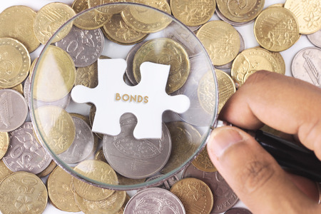 bonds: Hand of young businessman holding magnifying glass and white puzzle with BONDS  word on gold coins
