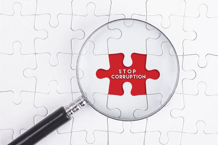 Bedrijfsconcept - vergrootglas op witte puzze met STOP CORRUPTIE Word