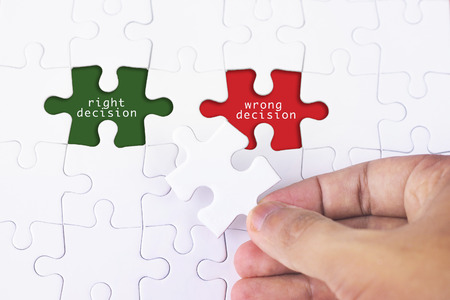 rightful: Business Concept - Female hand and missing puzzle with Right Decision - Wrong Decision word Stock Photo