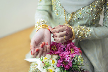 bride bangle: graceful poses of girls hand wearing gold bangles, with beatiful flower, selective focus shallow DOF Stock Photo