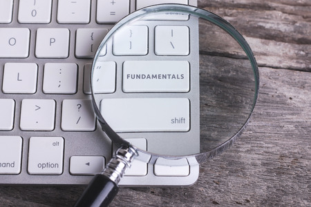 fundamentals: Business concept: FUNDAMENTALS on computer keyboard ans stethoscope on wooden background with copyspace area.