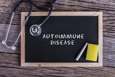 autoimmune: Stethoscope and Chalk board with inscription autoimmune disease on wooden background. Medical concept