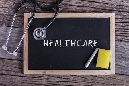 Stethoscoop en schoolbord met inscriptie gezondheidszorg op houten achtergrond. Medisch concept