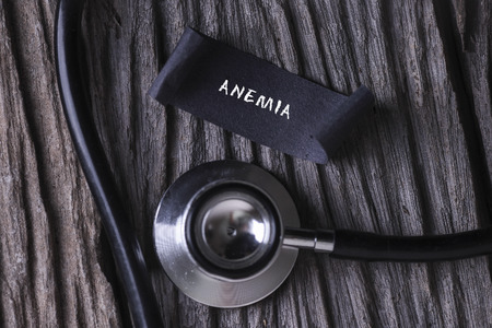 anemia: ANEMIA word written on label tag with Stethoscope on wood background Stock Photo
