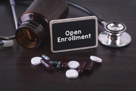 Stethoscoop, pil fles, diverse pillen, capsules en Open Inschrijving op houten achtergrond met copyspace gebied. Stockfoto