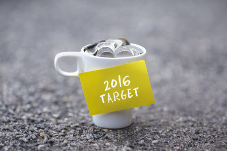 priceless: Coins in mug with 2016 TARGET label, blurred  at background.