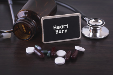 heart burn: Stethoscope, pill bottle, Various pills, capsules and Heart Burn on wooden background with copyspace area. Stock Photo