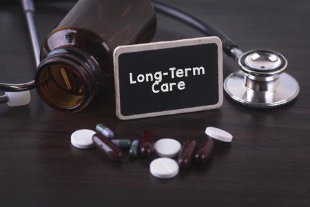 pflegeversicherung: Stethoskop, Pille Flasche, verschiedene Pillen, Kapseln und Langzeitpflege auf Holzuntergrund mit Exemplar Bereich.
