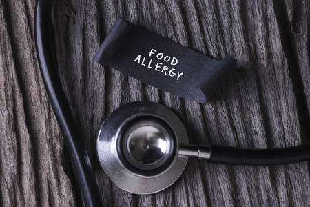 hypersensitivity: FOOD ALLERGY word written on label tag with Stethoscope on wood background Stock Photo