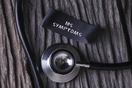 ibs: IBS SYMPTOMS word written on label tag with Stethoscope on wood background