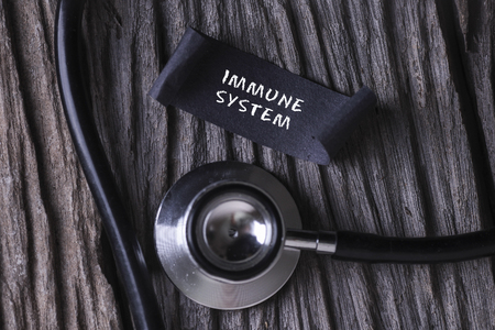 IMMUNE SYSTEM word written on label tag with Stethoscope on wood background