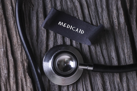 medicaid: MEDICAID word written on label tag with Stethoscope on wood background