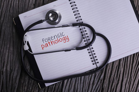 Forensic Pathology Word on Note book With Stethoscope on wooden background. Stock Photo