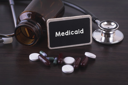 medicaid: Stethoscope, pill bottle, Various pills, capsules and Medicaid on wooden background with copyspace area. Stock Photo