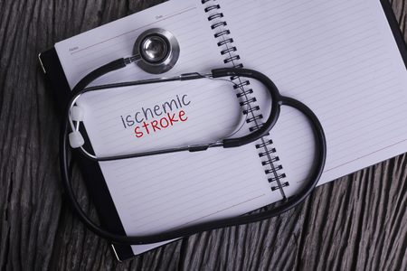 high damage: Ischemic Stroke Word on Note book With Stethoscope on wooden background. Stock Photo