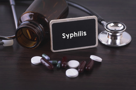 syphilis: Stethoscope, pill bottle, Various pills, capsules and Syphilis on wooden background with copyspace area. Stock Photo