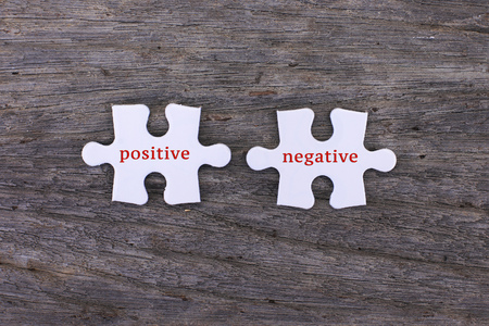 negative area: Missing white puzzle with positive negative word and copyspace area Stock Photo