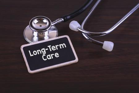 pflegeversicherung: Medizinische Konzept- Langzeitpflege Wörter auf Label-Tag mit Stethoskop geschrieben auf Holz Hintergrund