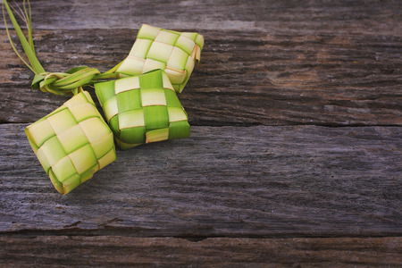 Ketupat (Rice Dumpling) On Wooden Background. Ketupat is a natural rice casing made from young coconut leaves for cooking rice during eid Mubarak 版權商用圖片