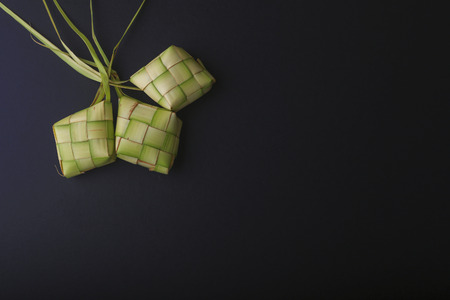 local festivals: Ketupat (Rice Dumpling) On Black Background. Ketupat is a natural rice casing made from young coconut leaves for cooking rice during eid Mubarak