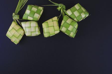 Ketupat (団子) 黒の背景に。Ketupat は若いココナッツから作られた自然米ケーシングのイード ムバラク中炊飯の葉